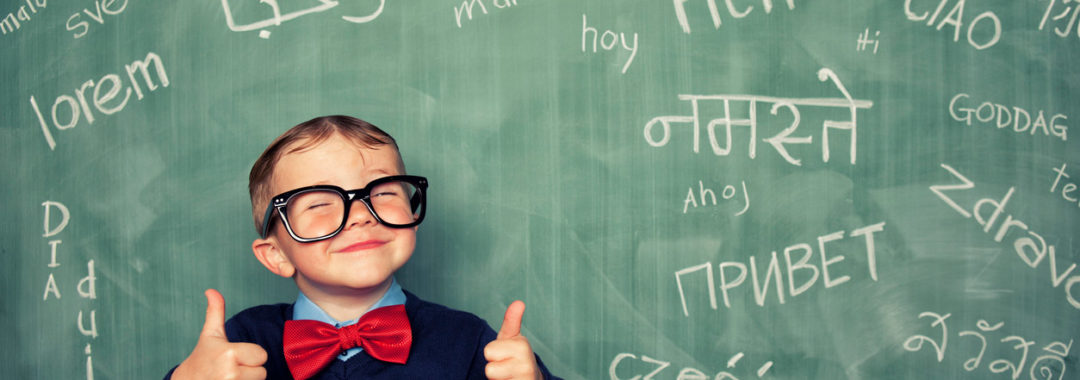 A young child smiling in front of a chalkboard filled with words in different languages